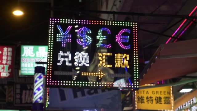 vidéos et rushes de pedestrians walk past a currency exchange store illuminated at night in the mong kok district of hong kong china on saturday oct 24 yen and dollar... - mong kok