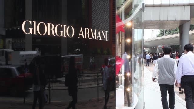 vídeos de stock, filmes e b-roll de pedestrians walk past a giorgio armani spa luxury store on canton road in the tsim sha tsui area of hong kong china on monday may 16 signage for... - giorgio armani marca de moda