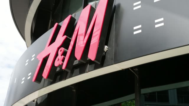 Pedestrians walk past a Hennes Mauritz AB fashion store in Frankfurt Germany on Wednesday July 16 2014 General views HM signage General views...