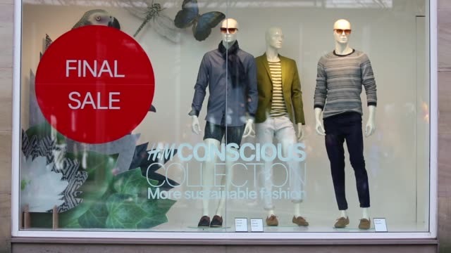 Pedestrians walk past a Hennes Mauritz AB fashion store in Manchester with sign in window display advertising 'Final Sale' Pedestrians pass by window...