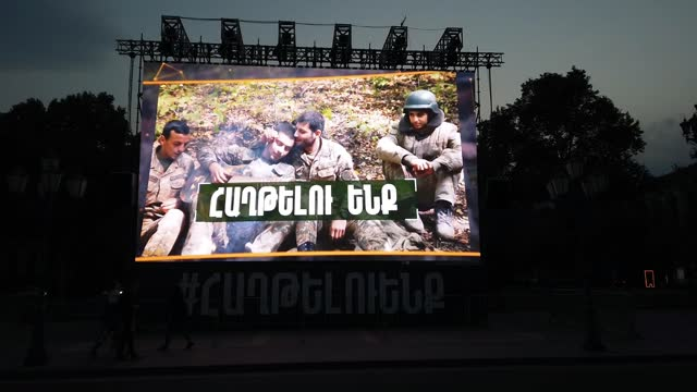 """pedestrians walk past a large monitor screen which plays a loop of armenian soldiers and with the hashtag """"we will win"""" during the military conflict... - eddie large stock videos & royalty-free footage"""