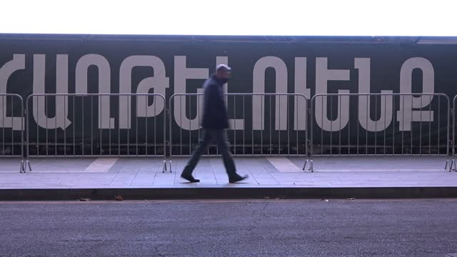 """pedestrians walk past a large monitor screen which plays a loop of armenian soldiers and with the hashtag """"we will win"""" on november 2020, in yerevan,... - eddie large stock videos & royalty-free footage"""