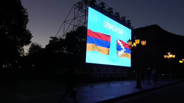 pedestrians walk past a large monitor screen which shows the flag of nagorno-karabakh known also as the artsakh republic and the flag of armenia with... - eddie large stock videos & royalty-free footage