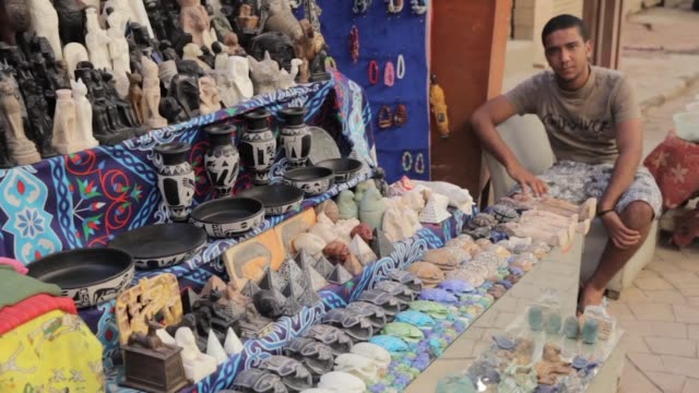vidéos et rushes de pedestrians walk past a market stall and shuttered shops in an empty souk in luxor, a shopkeeper sits alongside a display of souvenirs at a market... - souvenirs