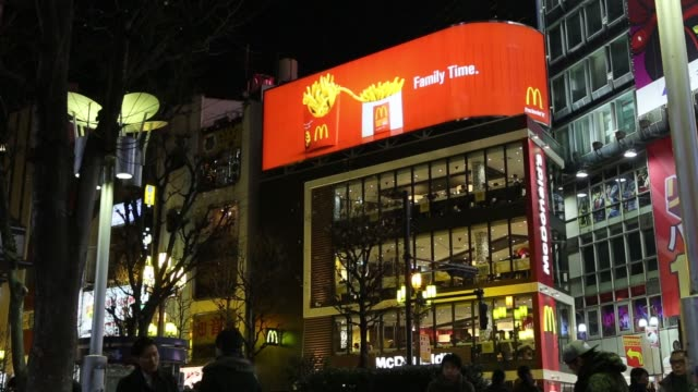 Pedestrians walk past a McDonald's restaurant operated by McDonald's Holdings Co Japan Ltd in Tokyo Japan An illuminated advertisement for McDonald's...