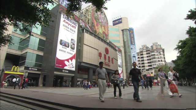 pedestrians walk past a modern shopping mall. - guangzhou stock videos & royalty-free footage