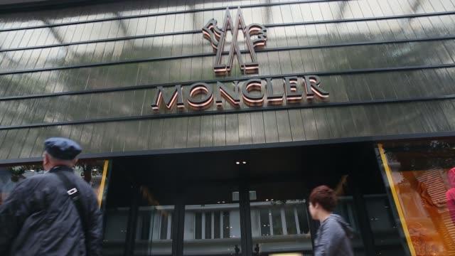 vídeos de stock, filmes e b-roll de pedestrians walk past a moncler store in the causeway bay district of hong kong china on wednesday april 30 2014 - ilha de hong kong