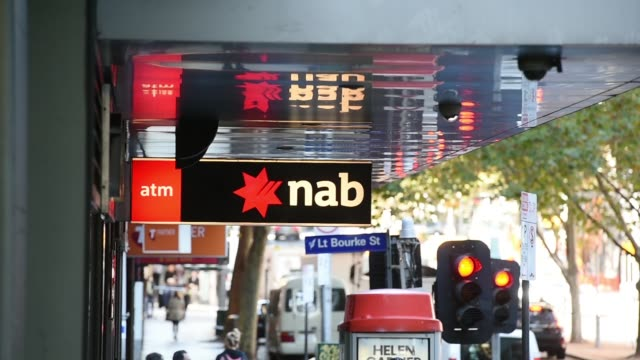 pedestrians walk past a national australia bank ltd branch in melbourne australia on monday may 2 the national australia bank ltd logo is displayed... - banking stock videos & royalty-free footage