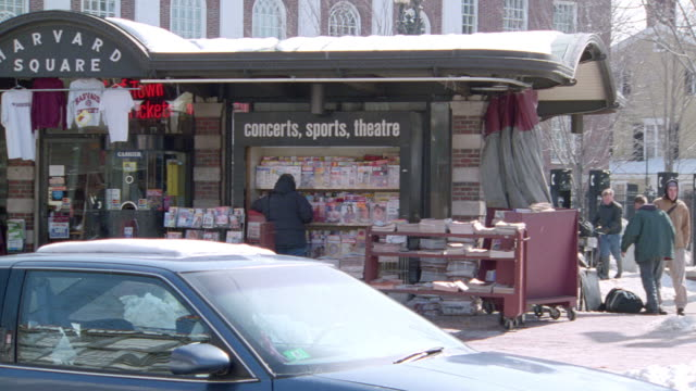 pedestrians walk past a newsstand and information center in harvard square in cambridge, massachusetts. - boston massachusetts stock-videos und b-roll-filmmaterial