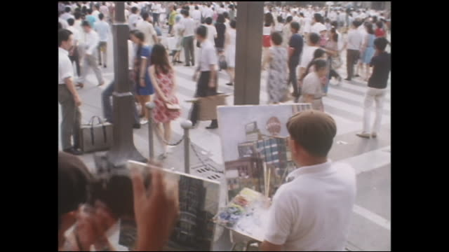 pedestrians walk past a painting artist during the pedestrian paradise. - showa period stock videos & royalty-free footage