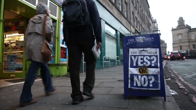 Pedestrians walk past a Scotsman newspaper advertising board with the headline 'Yes Or No' outside a newsagents in Edinburgh UK on Tuesday Sept 16...