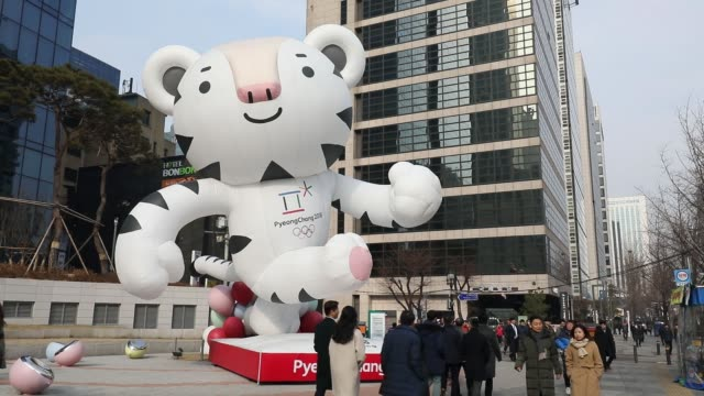 Pedestrians walk past a statue of the 2018 PyeongChang Winter Olympic Games mascot Soohorang outside a KEB Hana Bank branch in Seoul South Korea on...