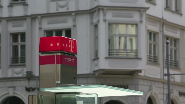 stockvideo's en b-roll-footage met pedestrians walk past a t mobile fixed line telephone box operated by deutsche telekom ag in berlin germany on monday june 23 a logo for t mobile... - goede staat