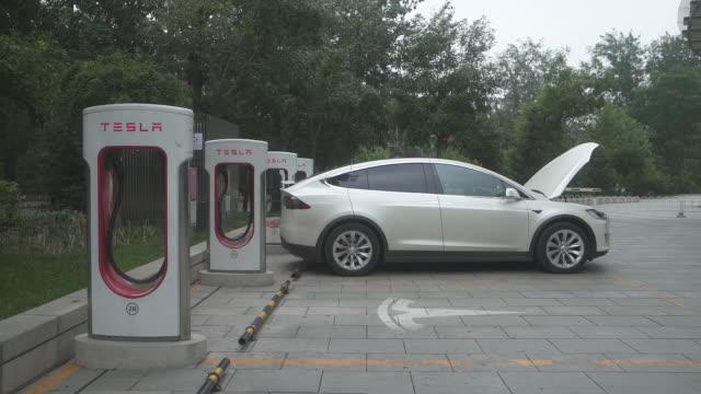 pedestrians walk past a tesla inc. showroom in beijing, china, on saturday, july 7, 2018. - alternative fuel vehicle stock videos & royalty-free footage