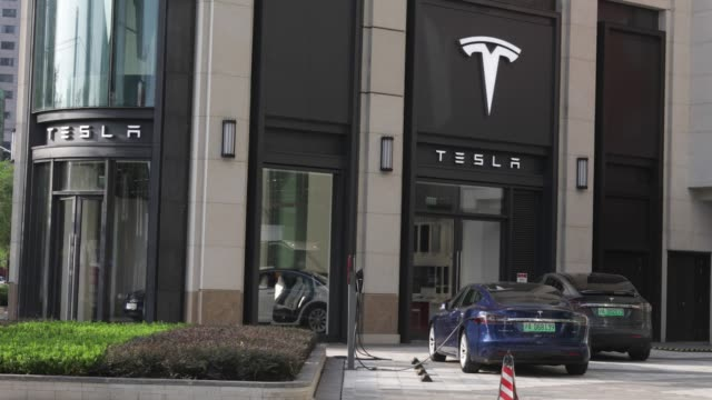 pedestrians walk past a tesla inc showroom in shanghai china on tuesday sept 12 a charging plug connects to a tesla inc model s electric vehicle... - charging sports stock videos & royalty-free footage