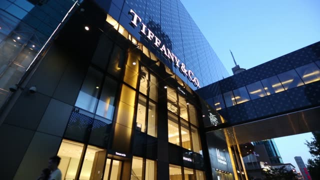 Pedestrians walk past a Tiffany Co store as it stands illuminated at night in Shanghai Pedestrians walk past a Cartier store operated by Cie...
