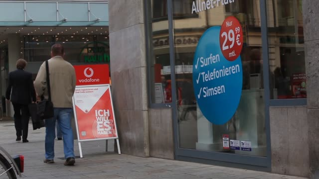 pedestrians walk past a vodafone store operated by vodafone group plc in leipzig germany on thursday sept 12 low angle view vodafone signage... - plc stock videos & royalty-free footage