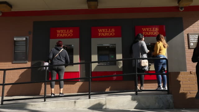 pedestrians walk past a wells fargo co bank branch and customers use atms in santa monica california us on monday march 25 2019 - wells fargo stock videos and b-roll footage