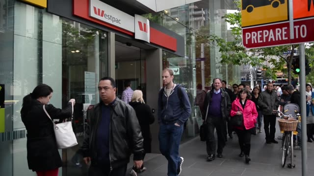 pedestrians walk past a westpac banking corp branch in melbourne australia on friday oct 11 the westpac banking corp sign and logo is displayed... - banking sign stock videos & royalty-free footage