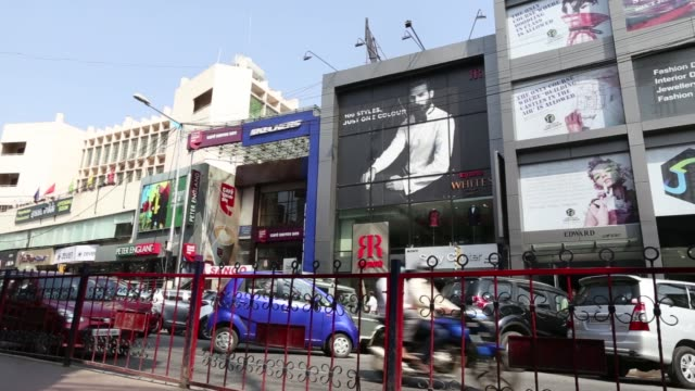 pedestrians walk past advertisements and signage hanging along a commercial street in bengaluru, india, on thursday, oct. 27 pedestrians walk past a... - levi's stock videos & royalty-free footage