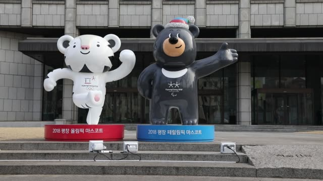 Pedestrians walk past an advertisement and statues of the 2018 PyeongChang Winter Olympic Games mascot Soohorang left and Bandabi right displayed...