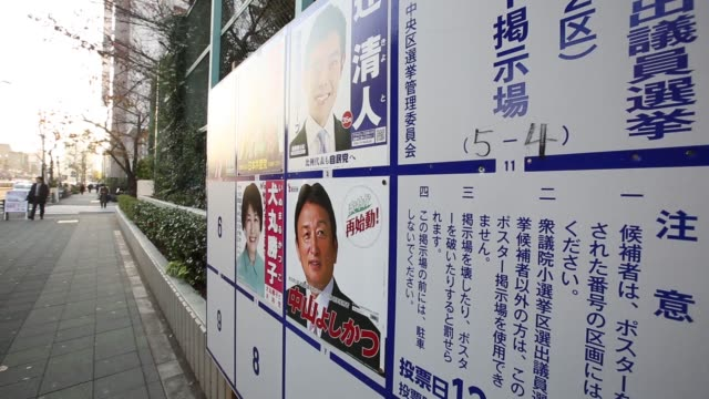 pedestrians walk past an advertisement board displaying posters of candidates for the dec 14 lower house election in tokyo japan on monday dec 8 2014 - 選挙点の映像素材/bロール