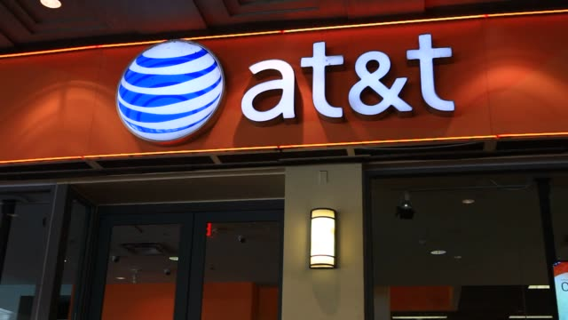 Pedestrians walk past an ATT store in Washington DC US on Tuesday April 21 2015 Shots Various close up shots of ATT signage above the entrance...