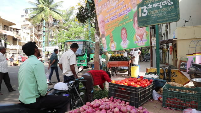 pedestrians walk past an election campaign billboard and customers shop for vegetables at a stall near an election campaign billboard in bengaluru... - election stock videos & royalty-free footage