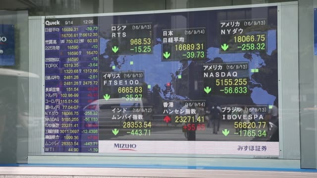 Pedestrians walk past an electronic stock board outside a securities firm in Tokyo Japan on Wednesday Sept 14 Pedestrians are reflected in an...