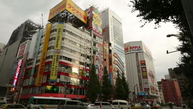 Pedestrians walk past an electronics store in the Akihabara district in Tokyo Japan on Thursday Nov 14 Commercial buildings housing electronics...