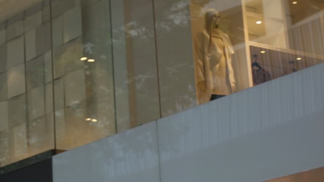Pedestrians walk past an HM store Pull focus inito a Hennes Mauritz AB logo is displayed above a store in the Tsim Sha Tsui area of Hong Kong Pan L R...
