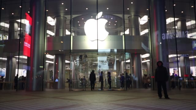 Pedestrians walk past and enter the Apple Inc store in the Wangfujing area of Beijing at night Inside Apple Inc Wangfujing Store on March 12 2013 in...