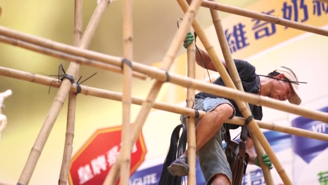 vidéos et rushes de pedestrians walk past bamboo scaffolding as they cross a street in the mong kok district of hong kong china on monday sept 12 workers climb a bamboo... - mong kok