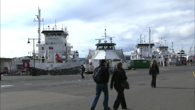 vídeos y material grabado en eventos de stock de pedestrians walk past boats anchored at a port in oslo, norway. - hombres de mediana edad