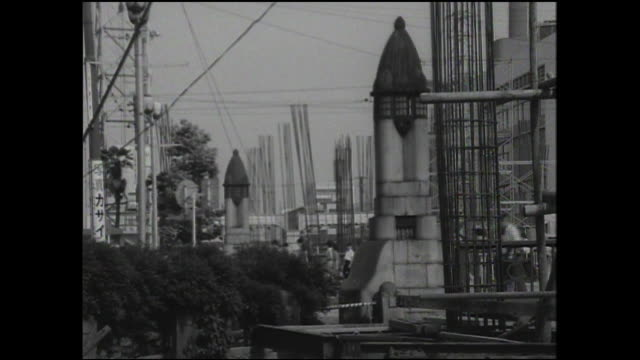 Pedestrians walk past construction scaffolds beside Kyobashi.