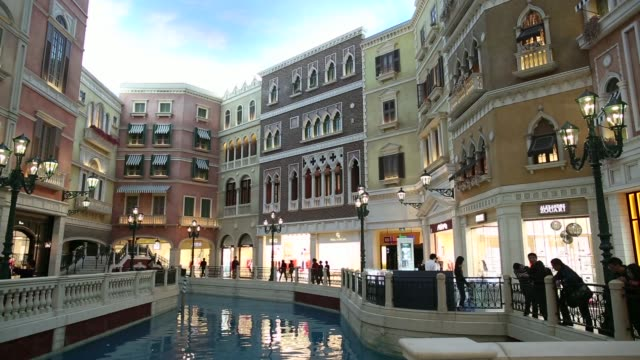 Pedestrians walk past Grand Canal Shoppes at the Venetian Macao resort and casino operated by Sands China Ltd a unit of Las Vegas Sands Corp in Macau...