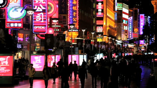 pedestrians walk past large neon signs above shops along nanjing road in shanghai, china. - nanjing road stock videos & royalty-free footage