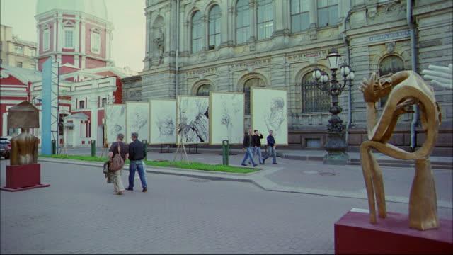pedestrians walk past modern art sculptures. - st. petersburg russia stock videos & royalty-free footage