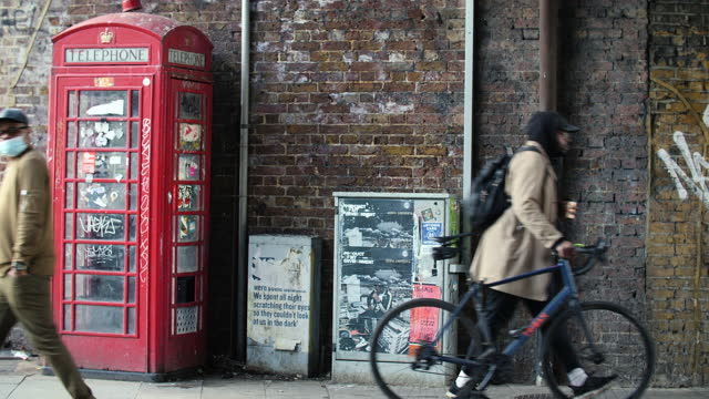pedestrians walk past old phone box in deptford, london - red stock videos & royalty-free footage