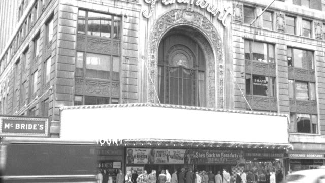pedestrians walk past or loiter in front of time square's paramount building. - アールデコ点の映像素材/bロール