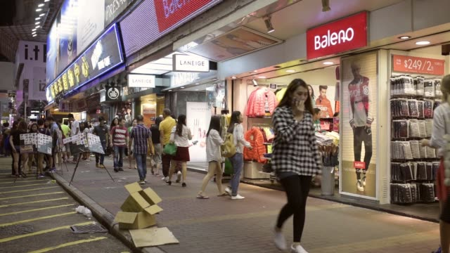pedestrians walk past shops and signage of stores at night in the mong kok district of hong kong china on saturday oct 24 vendors prepare snacks at a... - mong kok stock videos and b-roll footage