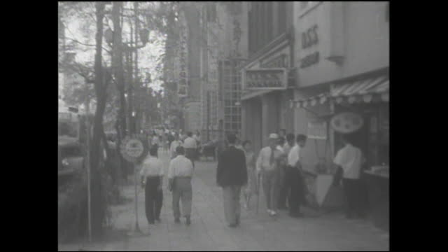 Pedestrians walk past shops on a Ginza sidewalk lined with willow trees.