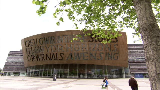 pedestrians walk past the cardiff millennium centre. available in hd. - cardiff wales stock videos & royalty-free footage