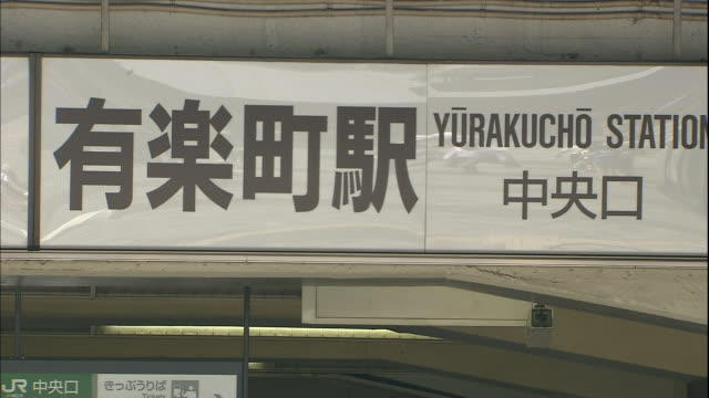 pedestrians walk past the entrance of yurakucho station in tokyo. - 日本語の文字点の映像素材/bロール