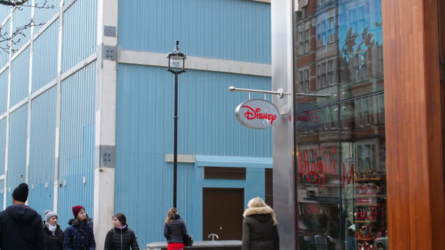 vídeos de stock e filmes b-roll de pedestrians walk past the exterior of the disney store on london's oxford street - sinal de loja
