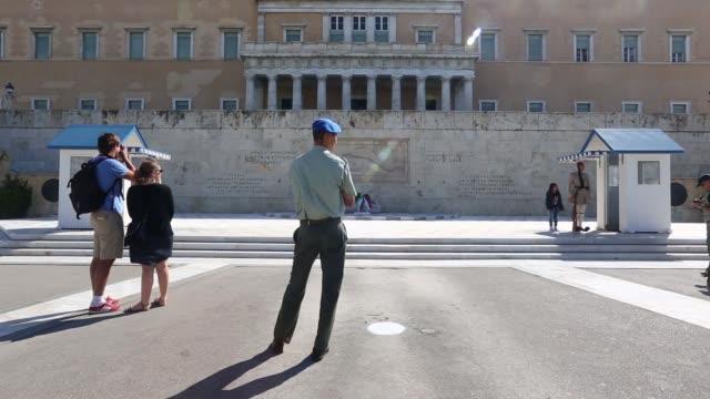 vidéos et rushes de pedestrians walk past the hellenic parliament building in athens greece on 29 sept 2014 tourists take photographs surrounded by pigeons in front of... - entourer