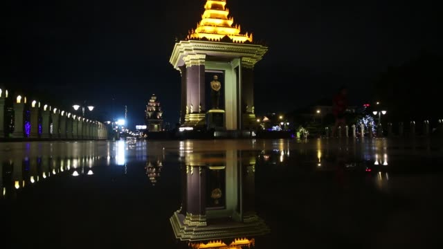 pedestrians walk past the illuminated king norodom sihanouk memorial as the independence monument is reflected in a puddle of water at night in phnom... - ナイトイン点の映像素材/bロール