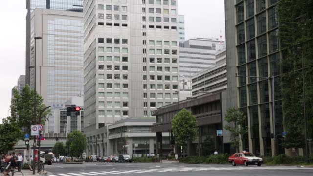 Pedestrians walk past the JX Building right and the Daiwa Gofukubashi Building all owned by Mitsubishi Estate Co standing in the Tokiwabashi district...