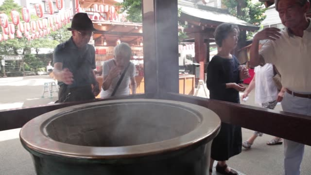 stockvideo's en b-roll-footage met pedestrians walk past the koganji temple in the sugamo jizo dori shopping area in tokyo japan on monday aug 1 visitors approach an incense bowl at... - soeplepel