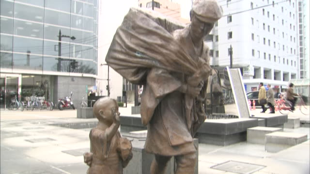 pedestrians walk past the statue of a medicine peddler and his child in front of the jr station in toyama, japan. - toyama prefecture stock videos and b-roll footage